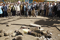 Kenya. Rift Valley province. Nakuru. 25.01.2008. A mob of Kikuyus (men, women and children) looks at the body of a dead black man from the Kalenjin tribe. The man, lying on the ground, was lynched by a group of men, stoned to death and his body set on fire. Inter-ethnic strife. Ethnic cleansing and purification. Capital offense. The Kikuyus are Kenya's most populous ethnic group. Kalenjin is another ethnic group of Nilotic origin living in the Great Rift Valley in western Kenya. © 2008 Didier Ruef