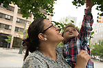 17 month old toddler boy reaching to touch leaf held by mother, outside