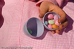 closeup of preschool child's hand holding open plastic colored Easter egg with jelly beans candy inside horizontal