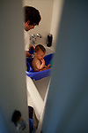 My husband gives our younger son, almost one, a bath.