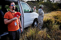 An American journalist and two guards stand to attention as the US national anthem is played out of tannoy speakers during a media tour of the now abandoned Camp X-ray at the American naval base at Guantanamo Bay, where over 600 alleged al Qaeda members have been held indefinitely. Described by the US as 'unlawful enemy combatants', they were captured primarily in Afghanistan during the 'war against terror'.