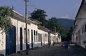 Paraty, Brazil. Colonial buildings in the village with a bicycle and a woman with her child.