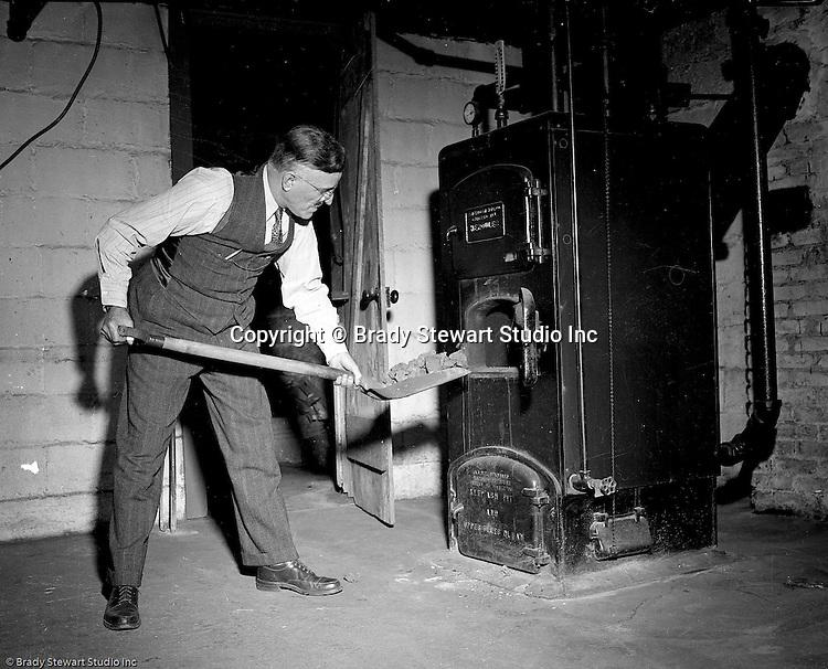 Wilkinsburg PA:  View of Brady Stewart loading coal into his Sears Hercules Coal Furnace at 1007 East End Avenue in Wilkinsburg.