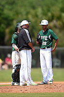 Farmingdale State Rams head coach talks with pitcher David Otero Jr. (28) and catcher Ryan Jordan (31) during a game against the U-Mass Boston Beacons at North Charlotte Regional Park on March 19, 2015 in Port Charlotte, Florida.  U-Mass Boston defeated Farmingdale 9-5.  (Mike Janes/Four Seam Images)
