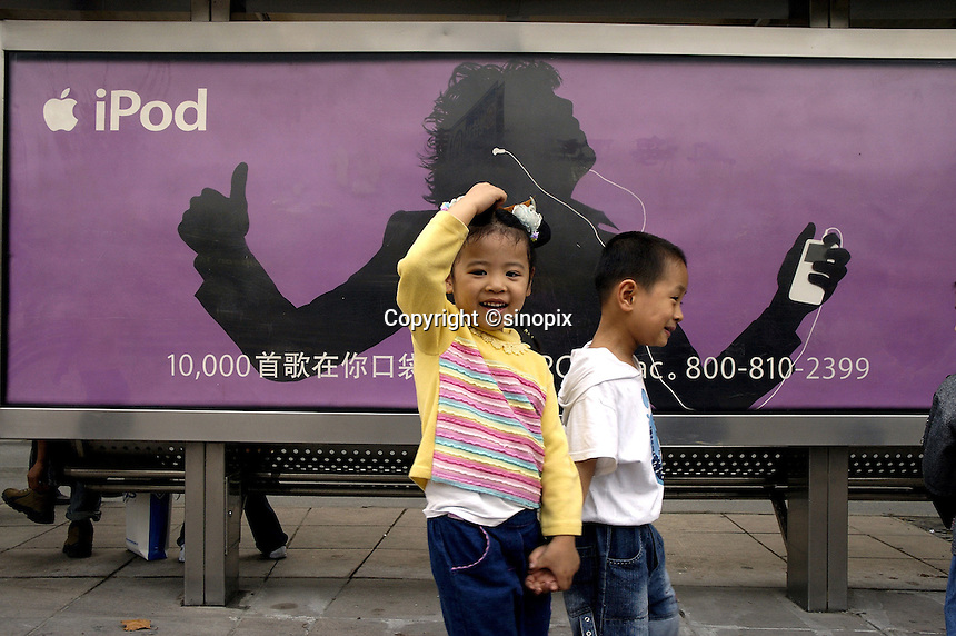 Children passing advertising for Apple iPod on a bus stop downtown.