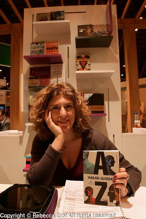 Publications Director of Turkish publishers Dogan Kitap, Deniz Yuce Basarir, holding a book by Hakan Gunday at the London Book Fair 2012