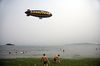 A Goodyear Blimp flies over swimmers in the algae-covered Qingdao Bay off the Number 6 Bathing Beach in Qingdao, Shandong, China...Qingdao is the host of the sailing events for the 2008 Summer Olympics. Algae blooms like this have become common in inland lakes in China, often caused by high pollution in bodies of water.  The city is asking for help and forcing residents to take part in the cleanup effort before the Olympic events..