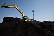 AnIndian worker is seen using the crane at the coal deposits of Adani Power at the Mundra Port in Gujarat, India.