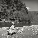1973. Senior woman and dog relaxing along Loyalsock Creek, PA.