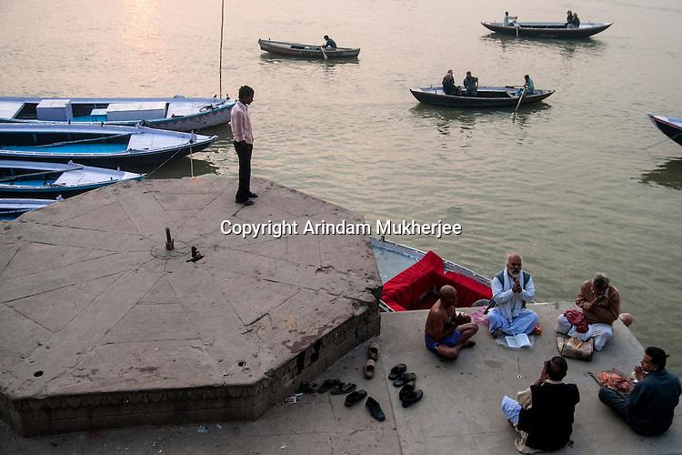 Indian men reads holy book at a ghat in Varanasi, Uttar Pradesh, India.