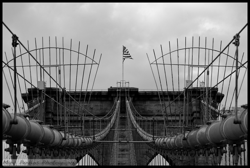 """I loved my visit to New York City, and walking across the Brooklyn Bridge was a highlight.  A strong wind was blowing, and the old brick, wood, and steel just cried out for photography.  This image focuses on the symmetry of cables and towers, with an American Flag blowing right at the viewer from the top of the tower.  I processed this in black and white to emphasize the dark, gritty feel of the old bridge.  The """"1875"""" date marker is easily visible in the image.  NOTE: This image has a black border embedded into it for web display; please contact me if you're interested in ordering this image so I can print it without a black border."""