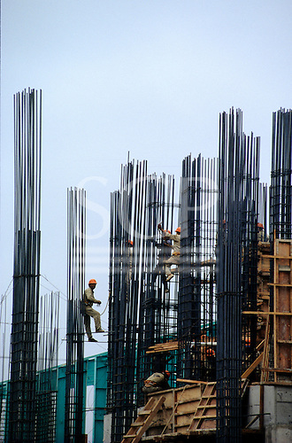 Lima, Peru. Construction workers with orange hard hats working on the steel reinforcements for concrete construction.