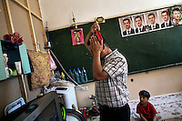 Abu Ammar combs his hair in a classroom which has become his family's home at a secondary school that has become a shelter for displaced persons, in Mashru Dummar, Damascus, Syria. The school now houses 65 families, mostly made of up of women and children.