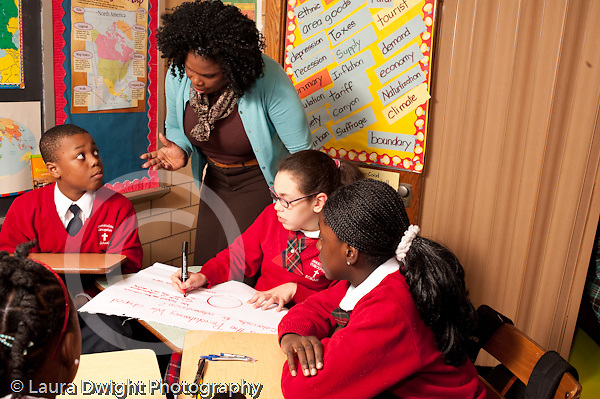 K-8 Parochial School Bronx New York Grade 5 social studies students working in small groups female teacher checking in with group horizontal