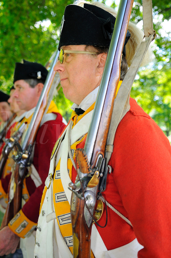 British redcoats of the Ninth Regiment of Foot stand to attention during musket drill at a Revolutionary War re-enactment at Fort Ticonderoga, New York, USA.