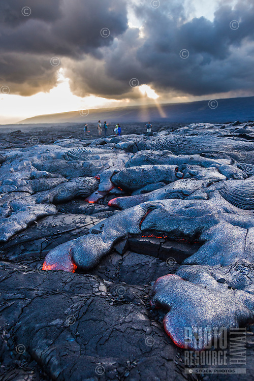 Visitors marvel at the glowing molten lava flowing down the hill while sun rays beam through distant clouds, Hawai'i Volcanoes National Park, Hawai'i Island.<br />