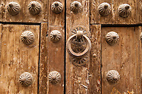 Traditional wooden door with brass knocker and ornamentation, Segovia, Spain