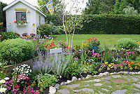 Cheerful backyard tiered flower perennial and annuals garden with lawn grass, patio stones, shed with bee insect theme