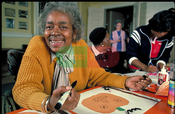 smiling elder woman working on crafts in nursing home