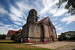 School children walk past the historic San Antonio de Padua Church, built in 1857, in the town of Lazi on the island of Siquijor, Philippines.