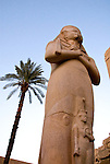 Luxor, Egypt -- A statue of Pharaoh Ramses III towers outside the temple to Ramses between the first and second pylons at Karnak Temple.  The small figure in front of the pharaoh would be his wife.  Karnak was built over many generations of Egyptian pharaoh, as each successive king added pieces to this temple honoring the most significant god of the ancient Egyptian pantheon, the god Amun (later, Amon-Ra), the sun god. © Rick Collier / RickCollier.com