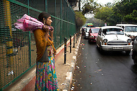 12 year old Ram Pyari waits to sell flowers at a busy crossing next to the flyover where she lives with her family.