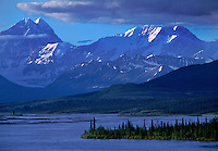 Snow-capped peaks of the Alaska Range rise beyond the Maclaren River along the Denali highway.