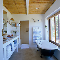 The bathroom has a ceiling of bamboo and a floor of polished concrete and the free-standing bath has spectacular views over the bay