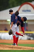 Lowell Spinners pitcher Kelvin Sanchez (35) leans on first baseman Ricardo Cubillan (44) to remove mud from his cleats during a NY-Penn League game against the Batavia Muckdogs on July 11, 2019 at Dwyer Stadium in Batavia, New York.  Batavia defeated Lowell 5-2.  (Mike Janes/Four Seam Images)