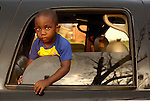 A young boy peers out of his family's car window before Waveland police officers and volunteers bring out his relatives who drown during hurricane katrina in Mississippi.
