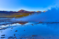 El Tatio geyser field (4320m), largest in Southern Hemisphere and highest in the world, at sunrise with mountain reflections, Atacama Desert Chile