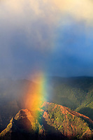 A thick and bright rainbow falls into the green and orange-red landscape of Waimea Canyon, Kaua'i.
