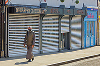 Pictured: A man wearing a face mask walks past closed shops in Swansea, Wales, UK. Thursday 26 March 2020<br /> Re: Covid-19 Coronavirus pandemic, UK.