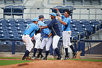 Charlotte Stone Crabs designated hitter Jace Conrad (23) is mobbed by teammates including Maxx Tissenbaum (8) and Willy Adames (2) after a walk off base hit during a game against the Dunedin Blue Jays on July 26, 2015 at Charlotte Sports Park in Port Charlotte, Florida.  Charlotte defeated Dunedin 2-1 in ten innings.  (Mike Janes/Four Seam Images)