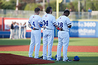 (L-R) Michael Russell (4), Bryce Hensley (34) and Jerry Downs (28) of the High Point Rockers stand for the National Anthem prior to the game against the Southern Maryland Blue Crabs at Truist Point on June 18, 2021, in High Point, North Carolina. (Brian Westerholt/Four Seam Images)