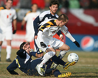 Casey Townsend #11of the University of Maryland loses the ball to Chase Tennant #7 of the University of Michigan during an NCAA quarter-final match at Ludwig Field, University of Maryland, College Park, Maryland on December 4 2010.Michigan won 3-2 AET.