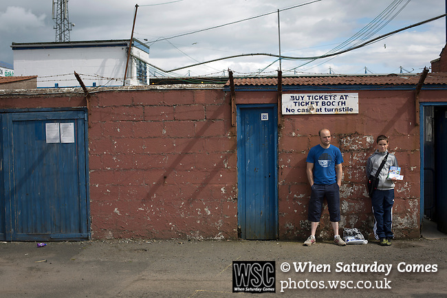Queen of the South 2 Stranraer 0, 11/08/2015. Scottish Challenge Cup first round, Palmerston Park. A programme seller and a man in a blue t-shirt outside one of the turnstiles at Palmerston Park, Dumfries, before Queen of the South hosted Stranraer in a Scottish Challenge Cup first round match. The game was the opening match of the season in a competition open to sides below the Scottish Premiership. Queen of the South won the match 2-0, watched by a crowd of 1229 spectators. Photo by Colin McPherson.