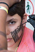 A Kayapo woman uses genipapo dye to paint a traditional design on the face of a visitor to the International Indigenous Games, in the city of Palmas, Tocantins State, Brazil. Photo © Sue Cunningham, pictures@scphotographic.com 25th October 2015