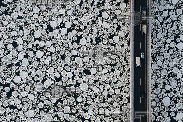 Cars and vans travel on a road past the ice covered Vistula River near the village of Kiezmark.
