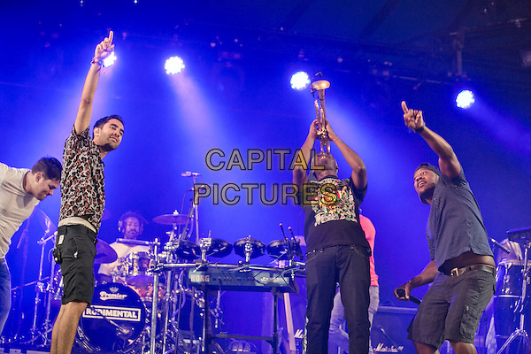 21st July 2013: UK electronic group Rudimental perform on the BBC6 Music stage on the last day of the 2013 Latitude Festival, Henham Park, Suffolk<br /> on stage in concert live gig performance performing music half length trumpet hand arm pointing <br /> CAP/PP/MM<br /> ©Mike Mustard/PP/Capital Pictures