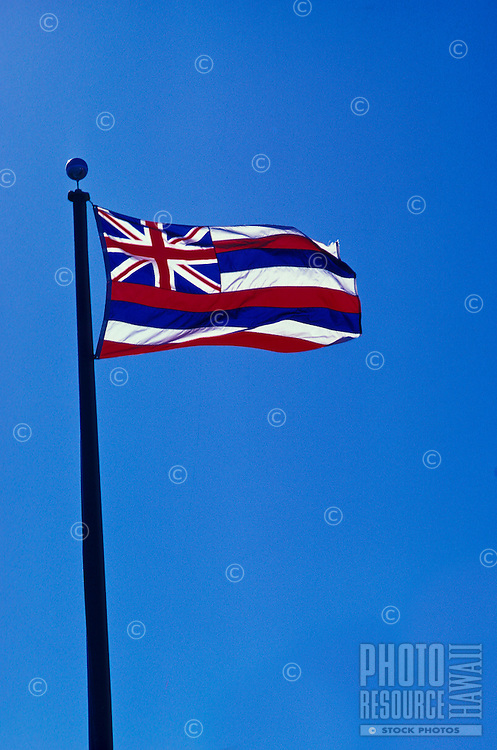 Hawaiian flag blowing in the wind with blue sky in background