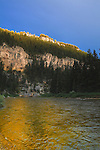 Sunlight on a rocky cliff reflects in the Smith River in Montana