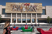 """Albania. Tirana. The National Museum of History on Skanderbeg Square. The National Museum of History is the national historical museum of Albania and the country's largest museum located in Albania. It was opened on 28 October 1981 and is 27,000 square metres in size, while 18,000 square metres are available for expositions. Above the entrance of the museum is a large mural mosaic titled The Albanians that depicts purported ancient to modern figures from Albania's history. The flag of Albania is a red flag with a silhouetted black double-headed eagle in the center. The red stands for bravery, strength and valor, while the double-headed eagle represents the sovereign state of Albania. The Skanderbeg Square is the main plaza in the centre of Tirana. The square is named after the Albanian national hero Gjergj Kastrioti Skënderbeu and the total area is about 40.000 square metres. The Skanderbeg Square is a pedestrian zone. Free Wifi offered by ALBtelecom SH. a. (a shortening of Albanian Telecom - """"Telekomi Shqiptar"""") which was established as Albania's state company that provided telecommunications services through a fixed and mobile network. Colorful giant plastic forms (red, blue, green) for people to sit and relax while surfing the web. Tirana is the capital and most populous city of the Republic of Albania. The city is also the capital of the surrounding county of Tirana, one of 12 constituent counties of the country. 27.5.2018 © 2018 Didier Ruef"""
