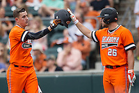 Oklahoma State Cowboys third baseman Craig McConaughy #40 is greeted by teammate Zach Fish #26 after he scored during the NCAA baseball game against the Texas Longhorns on April 26, 2014 at UFCU Disch–Falk Field in Austin, Texas. The Cowboys defeated the Longhorns 2-1. (Andrew Woolley/Four Seam Images)