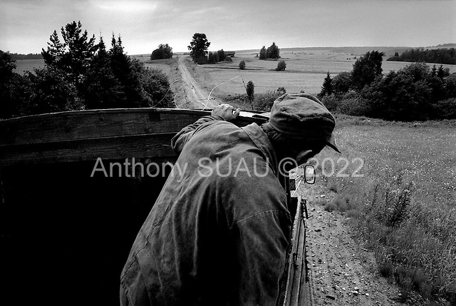 Permogorya, Russia  .1998.A collective of farmers leaves the fields at the days end and as a heavy rain sets in..
