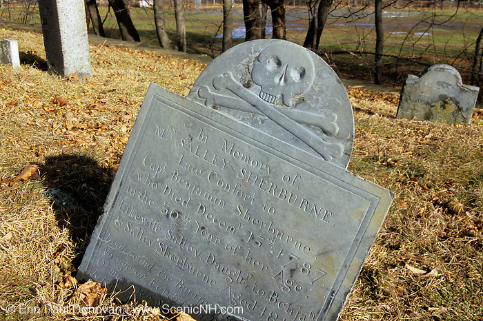 Old weathered skull and cross bones headstone from ground level at South Cemetery in Portsmouth, New Hampshire USA.