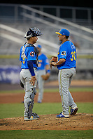Myrtle Beach Pelicans pitcher Javier Assad (30) talks with catcher Miguel Amaya (9) during a Carolina League game against the Potomac Nationals on August 14, 2019 at Northwest Federal Field at Pfitzner Stadium in Woodbridge, Virginia.  Potomac defeated Myrtle Beach 7-0.  (Mike Janes/Four Seam Images)