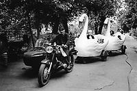 Kazakhstan. Semipalatinsk. Amusement park. A man riding a sidecar motorbike pulls two fake plastic swans carrying mothers and children.  Semey is the Kazakh name for Semipalatinsk and is located in the Eastern Kazakhstan Province. © 2008 Didier Ruef .