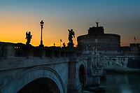 Saint Angelo Bridge and Castle during twilight, with Bernini angel sculpture silhouettes in the colorful sky above the Tiber, Vatican, Rome Italy