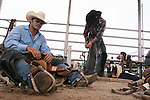 CHAD PILSTER •Hays Daily News<br /> <br /> Cody Anthony, left, Monahans, Texas, works on preparing his saddle while James Greeson, Huntsville, Texas, tightens his chaps on Monday, July 29, 2013, during the Graham County fair and Jayhawker Roundup Rodeo in Hill City, Kansas.
